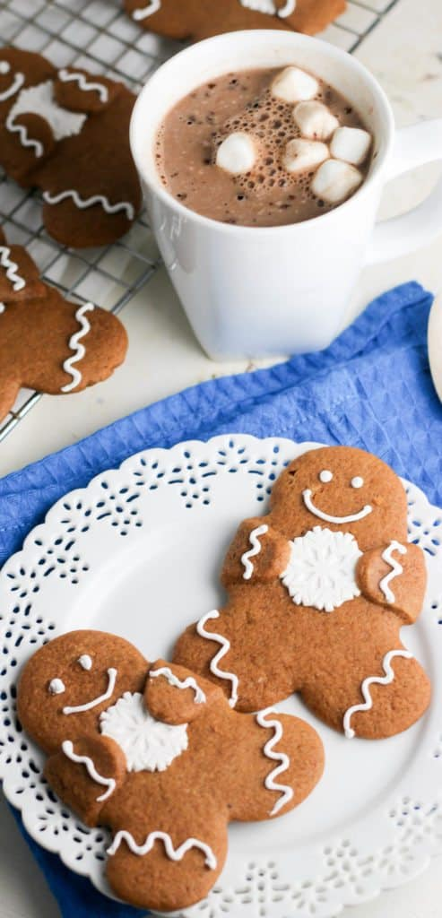 gingerbread cutout cookies on a plate with a cup of hot cocoa
