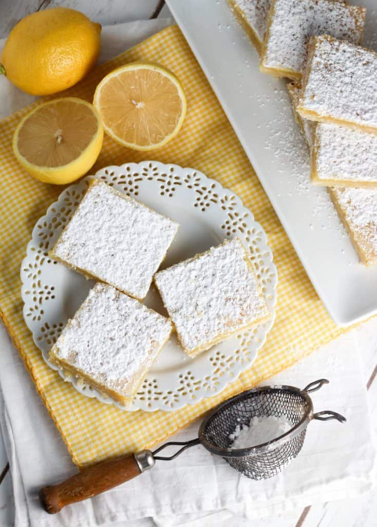 lemon bars on a plate with a lemon