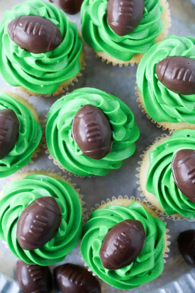 cupcakes with green frosting and chocolate footballs on top