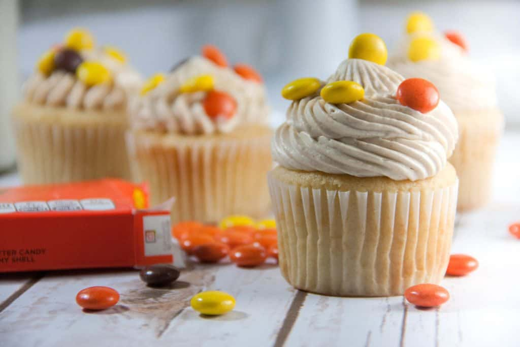 peanut butter cupcakes with Reese's on top and a box of reese's pieces