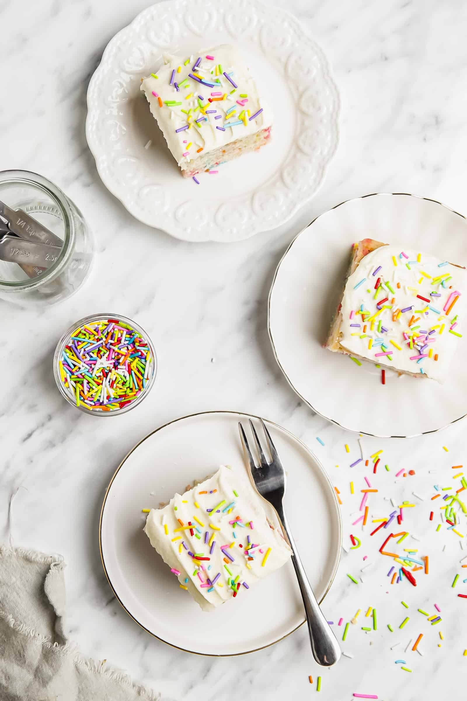 top down view of three slices of funfetti sheet on cake on a plate