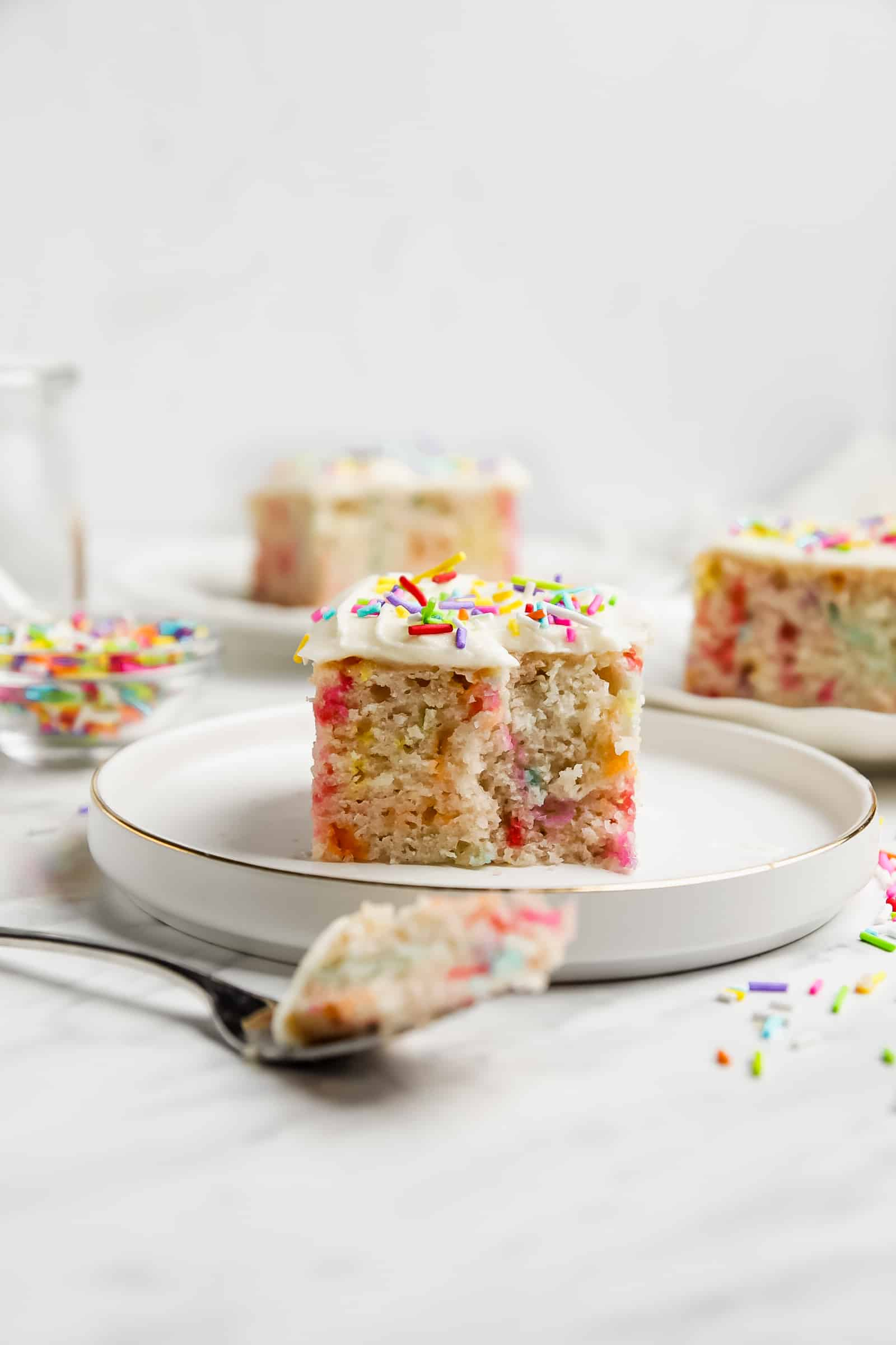 slice of funfetti cake on a plate with a fork