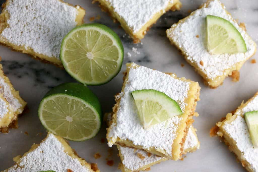 margarita bars and a lime on a marble cutting board