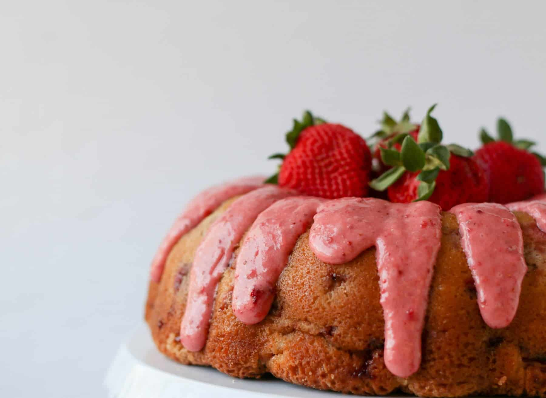 strawberry pound cake on a cake stand with fresh strawberries