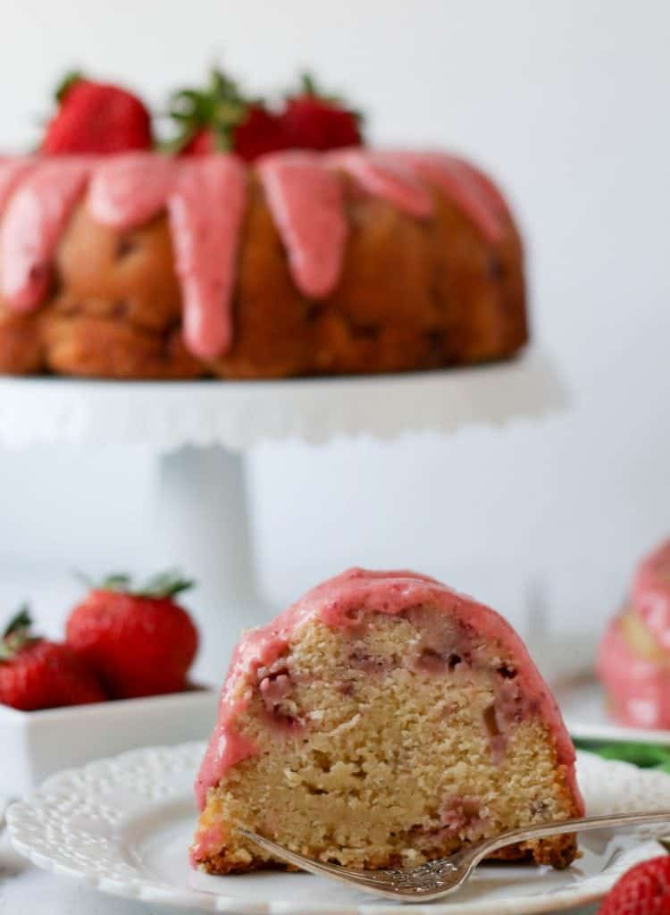 slice of strawberry pound cake on a plate with the cake in the background on the cake stand