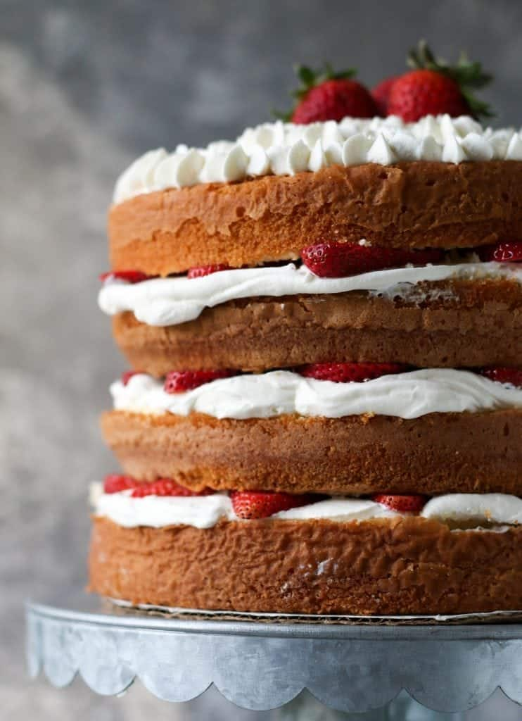 Four layer cake with whipped cream and strawberries
