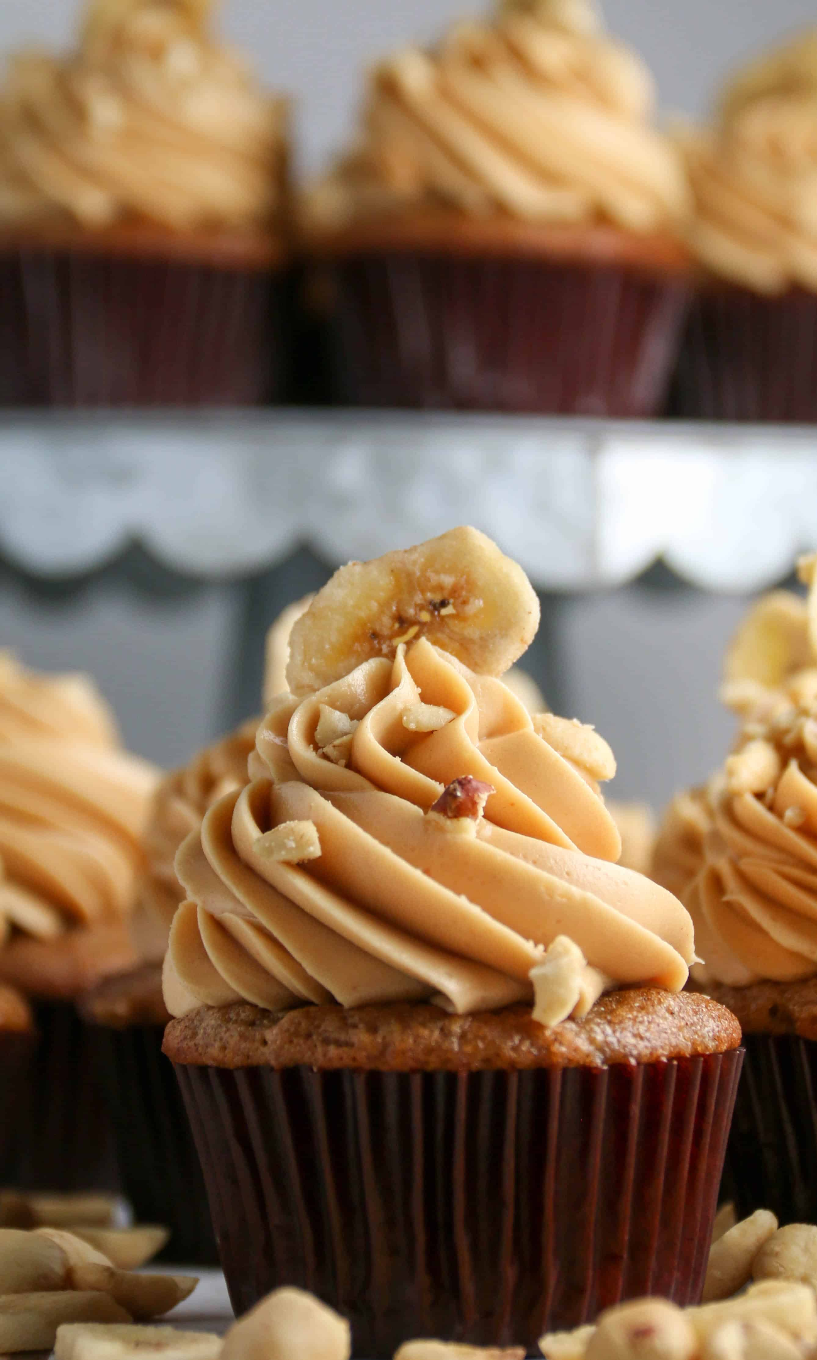 Banana cupcake with peanut butter frosting and cupcakes on a cake stand behind it