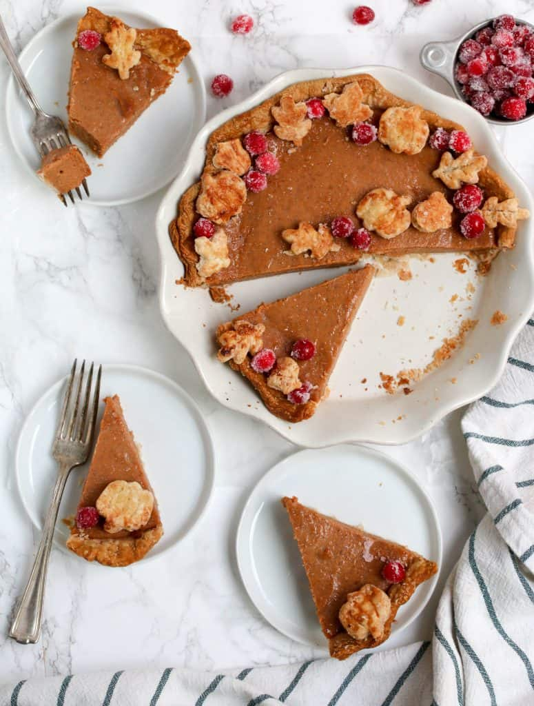 Pumpkin pie and three plates with slices on it