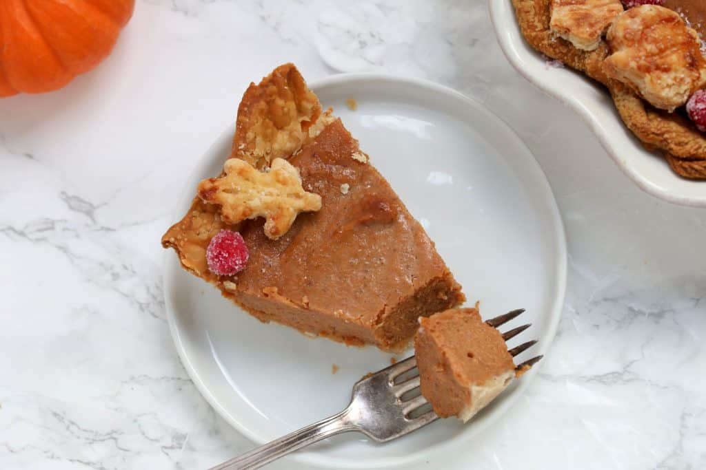 slice of pumpkin pie on a plate with a fork