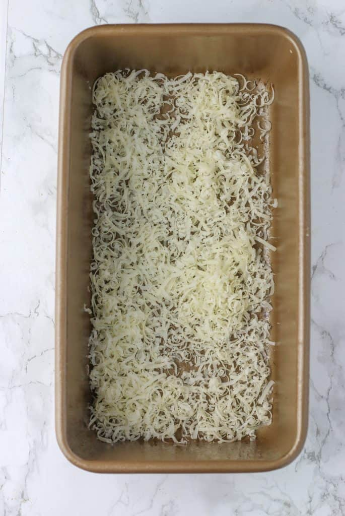 loaf pan with parmesan cheese sprinkled on the bottom