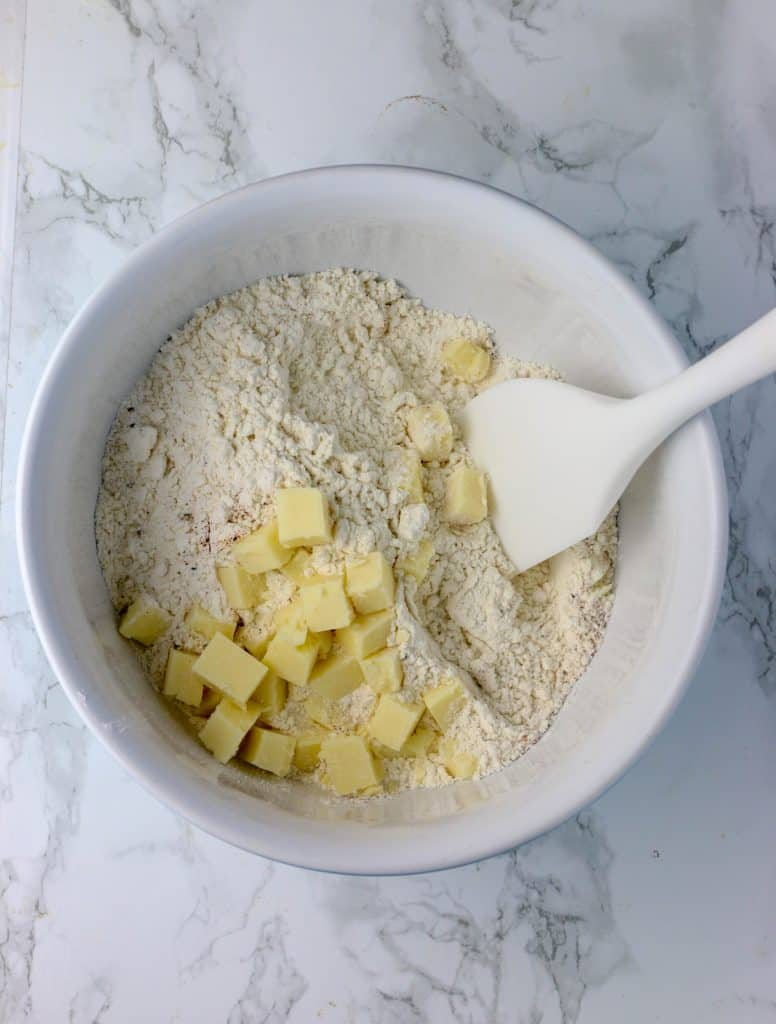 mixing bowl with dry ingredients and cubes of cheddar