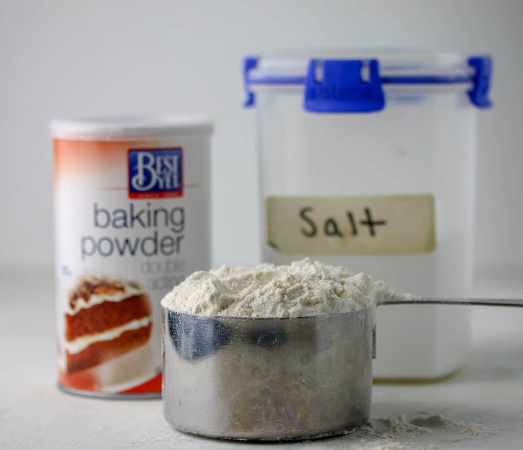 baking powder, container of salt, and a cup of flour