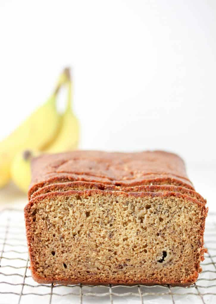 banana bread on a cooling rack with bananas in the background