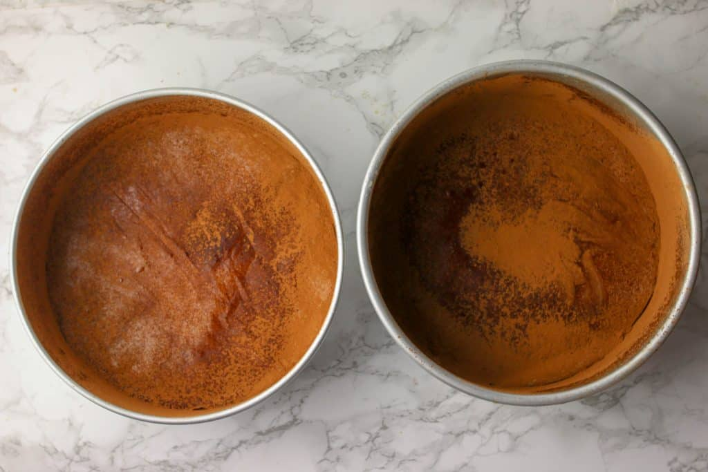 two cake pans dusted with cocoa powder