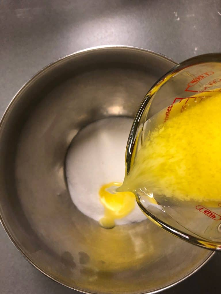 butter poured into sugar for furnfetti cupcakes
