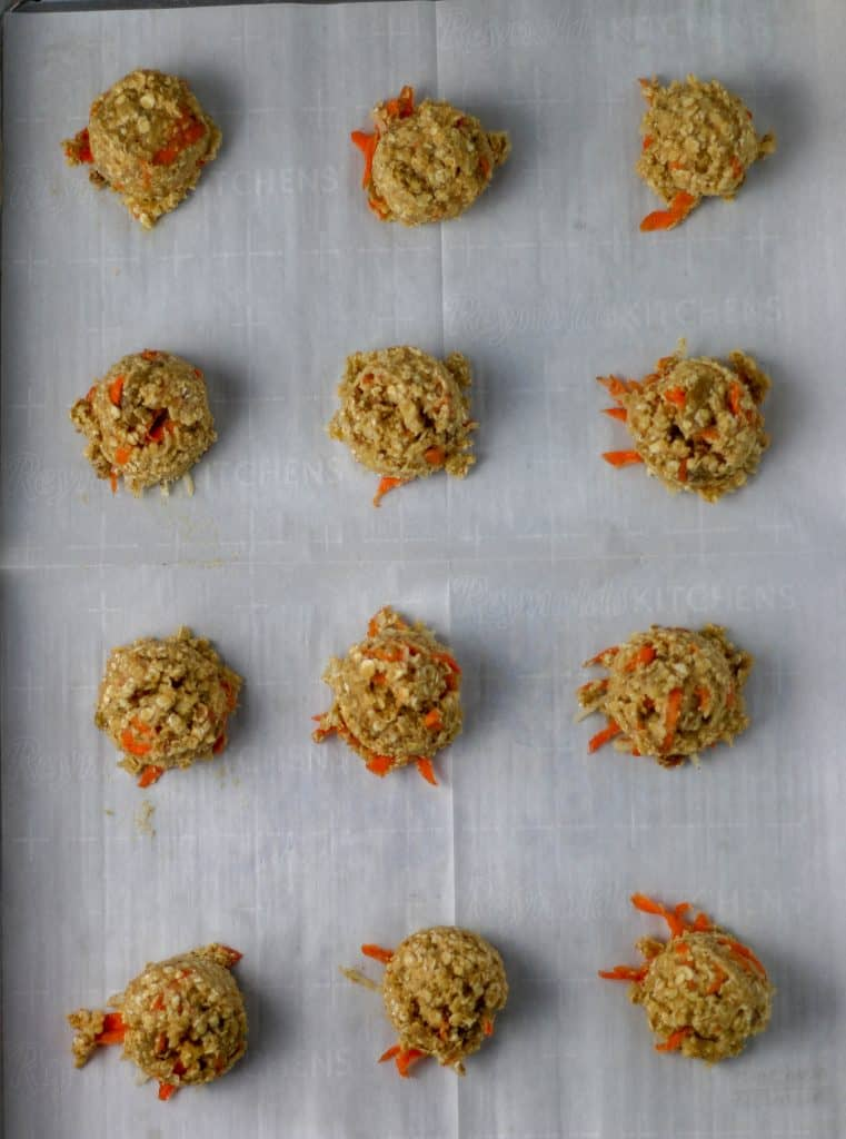 carrot cake cookie dough balls on a cookie sheet