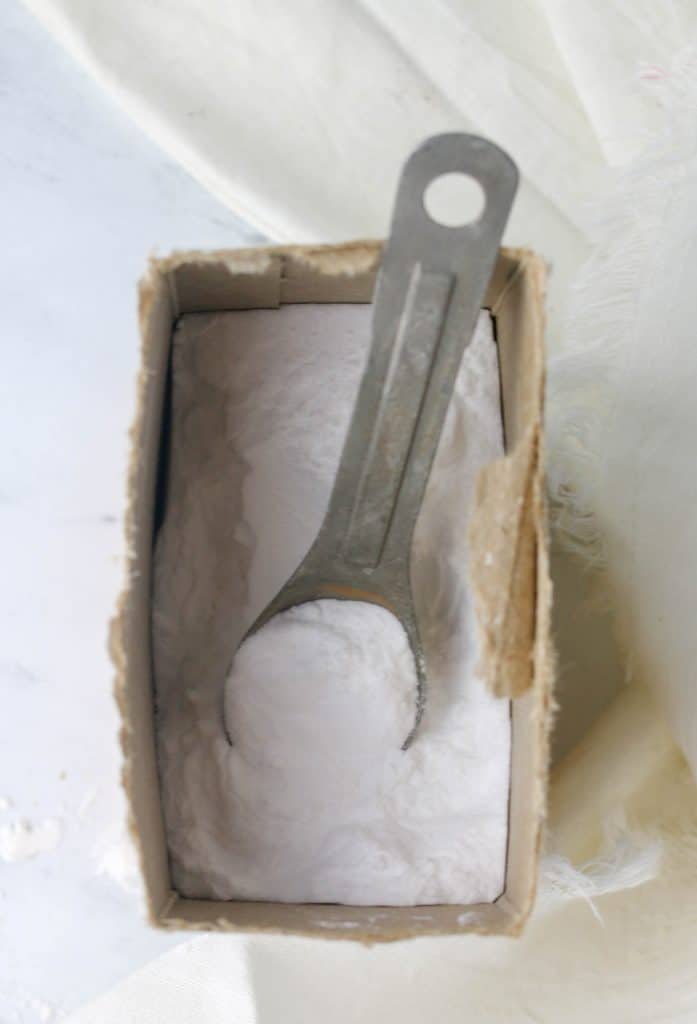 container of baking soda with a measuring spoon