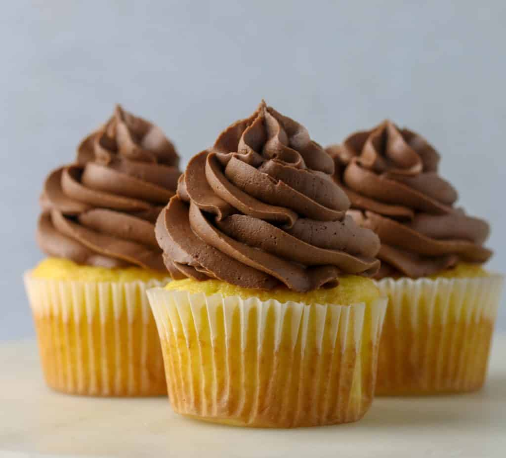 three vanilla cupcakes with chocolate buttercream frosting on top