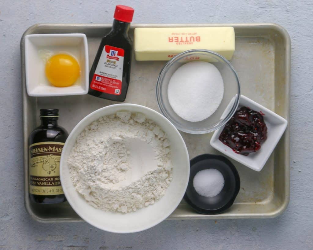 Ingredients for raspberry thumbprint cookies on a cookie sheet