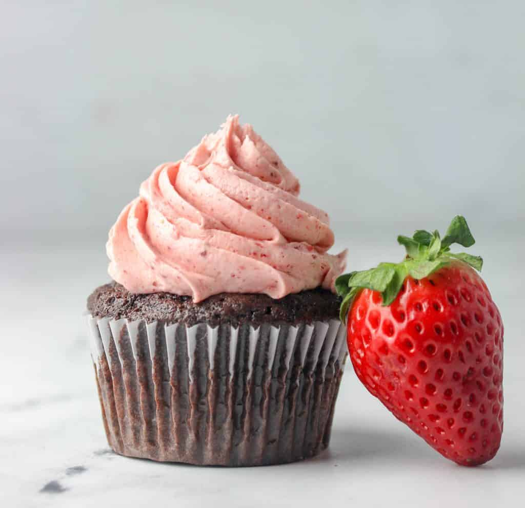 chocolate cupcake with strawberry frosting and a strawberry next to it