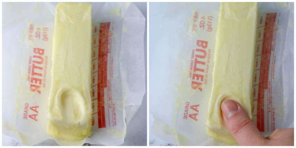 softened butter stick with a thumb indenting into it