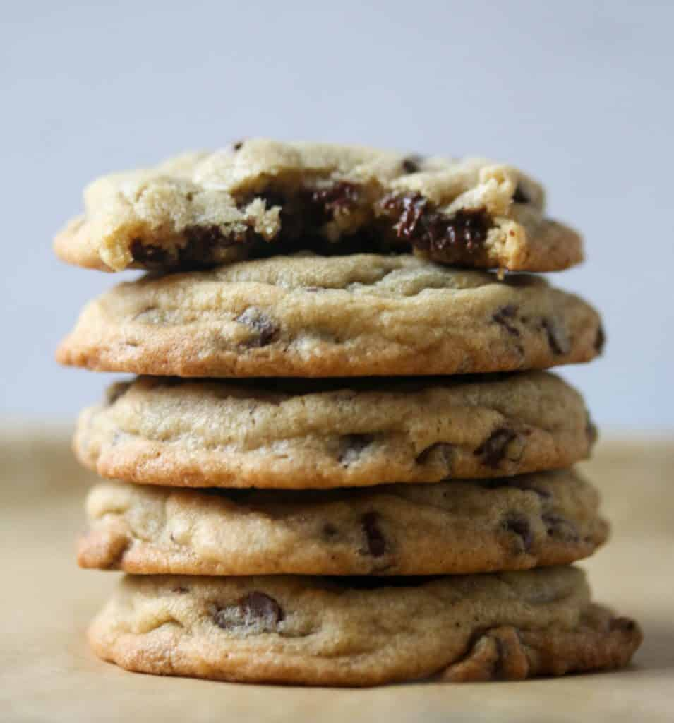 stack of chocolate chip cookies with the top cookie has a bite taken out of it