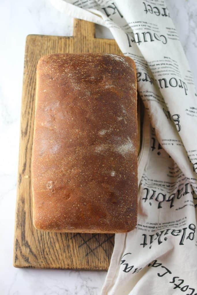 whole wheat sourdough sandwich bread loaf on a cutting board