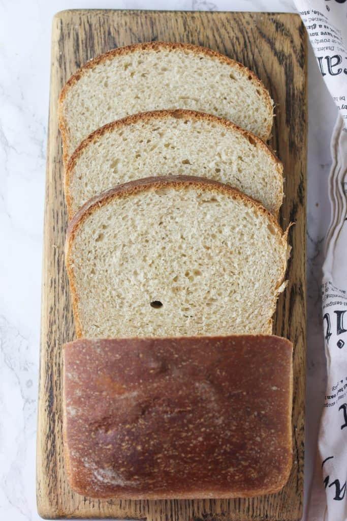loaf of whole wheat sourdough bread sliced on a cutting board