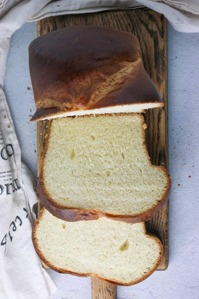 loaf of brioche bread sliced on a cutting board