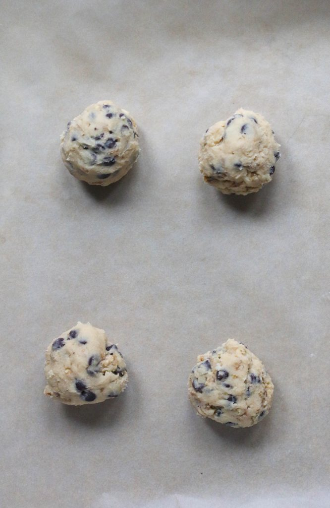 four balls of cookie dough on parchment paper
