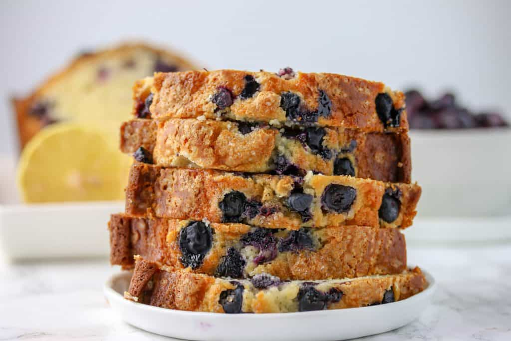 slices of blueberry bread stacked on a plate