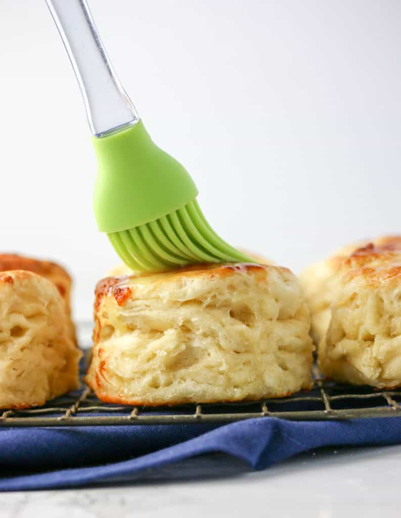 biscuit brushed with butter by a green silicone brush
