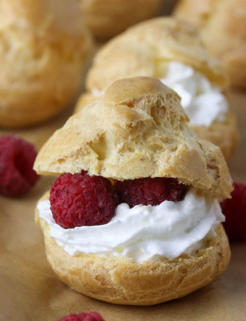 cream puff filled with whipped cream and rasperries