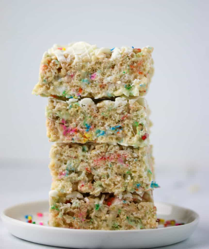 four white chocolate rice krispie treats stacked on a plate