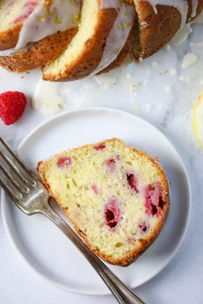 slice of lemon raspberry bundt cake on a plate with a fork