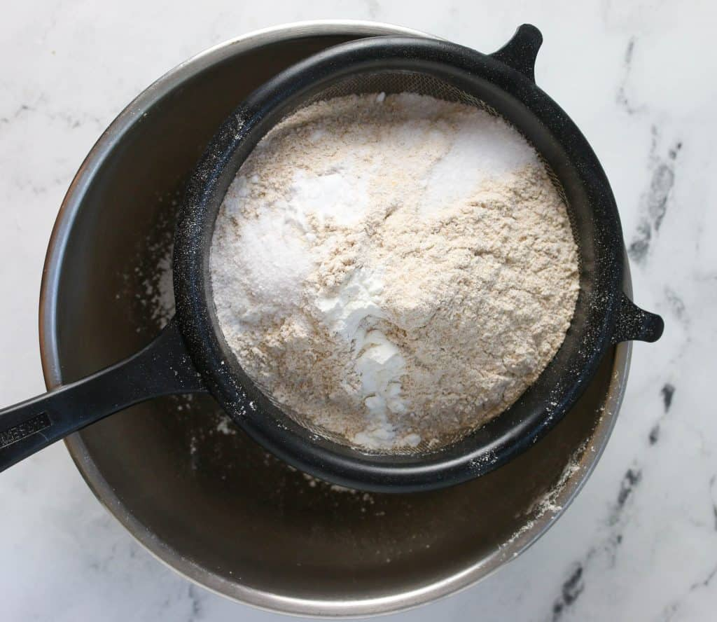 sifter set over mixing bowl with dry ingredients in it