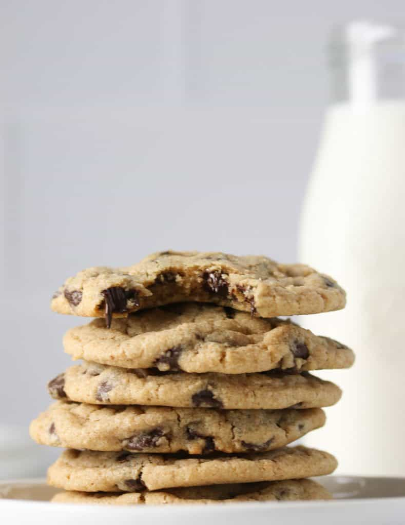 stack of whole wheat chocolate chip cookies with a glass of milk behind it