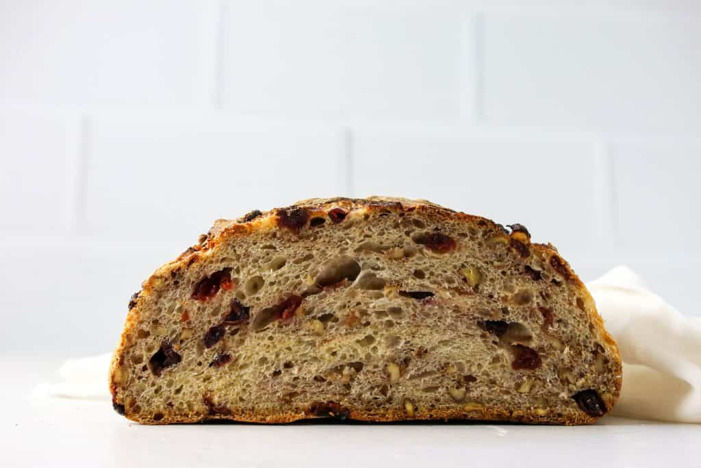 no knead cranberry pecan bread loaf cut in half