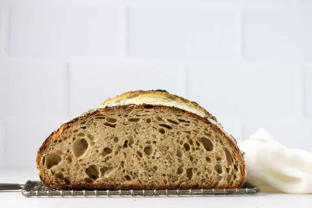 sourdough rye bread cut in half on a cooling rack