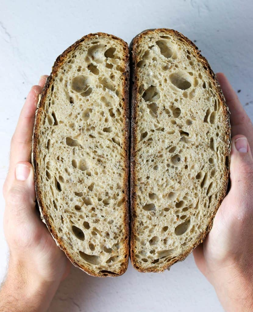 hands holding a loaf of sourdough rye bread cut in half
