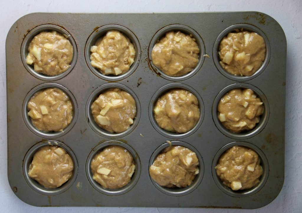 apple muffin batter scooped into muffin tins