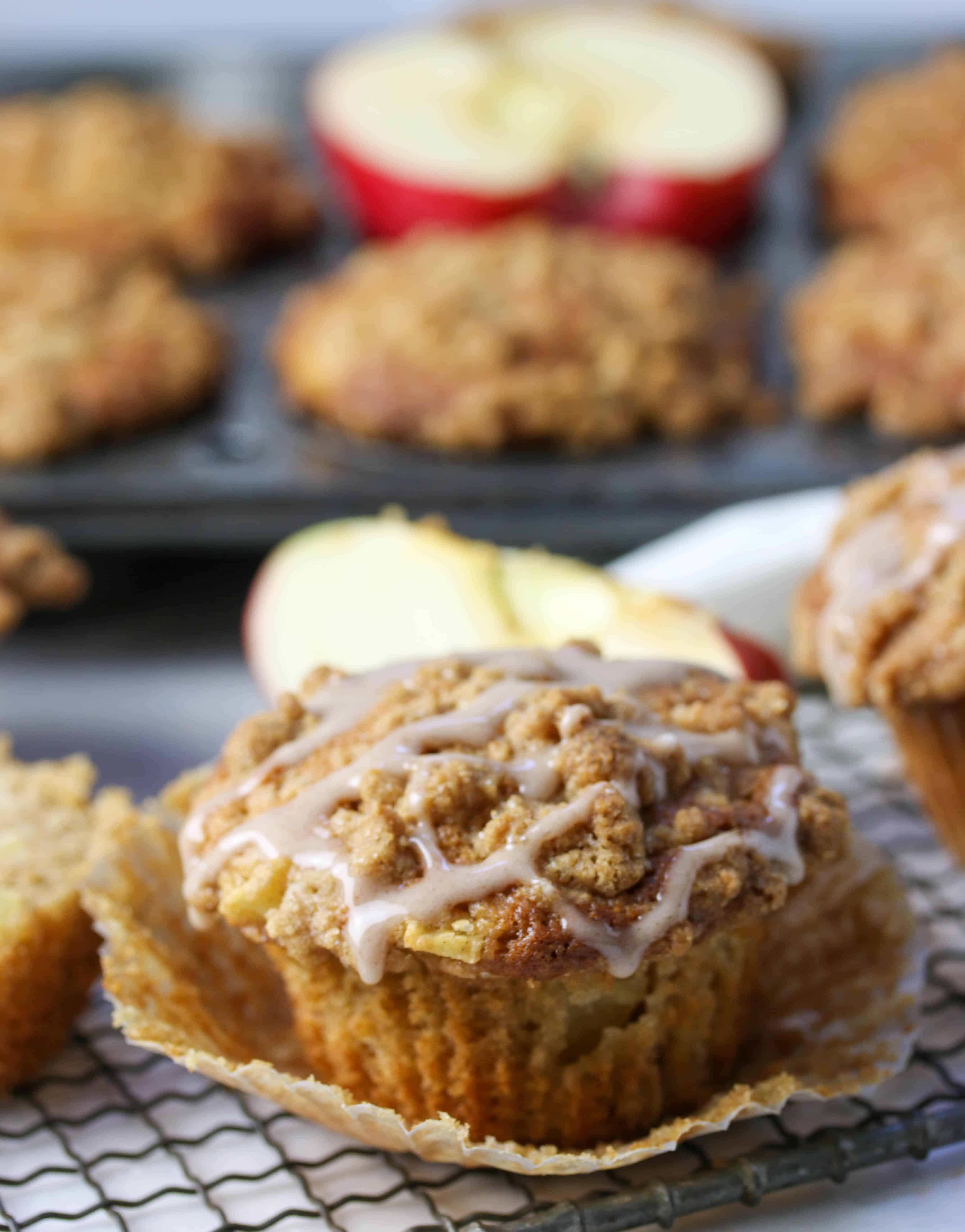 apple crumb muffin with glaze and muffin liner peeled away from it