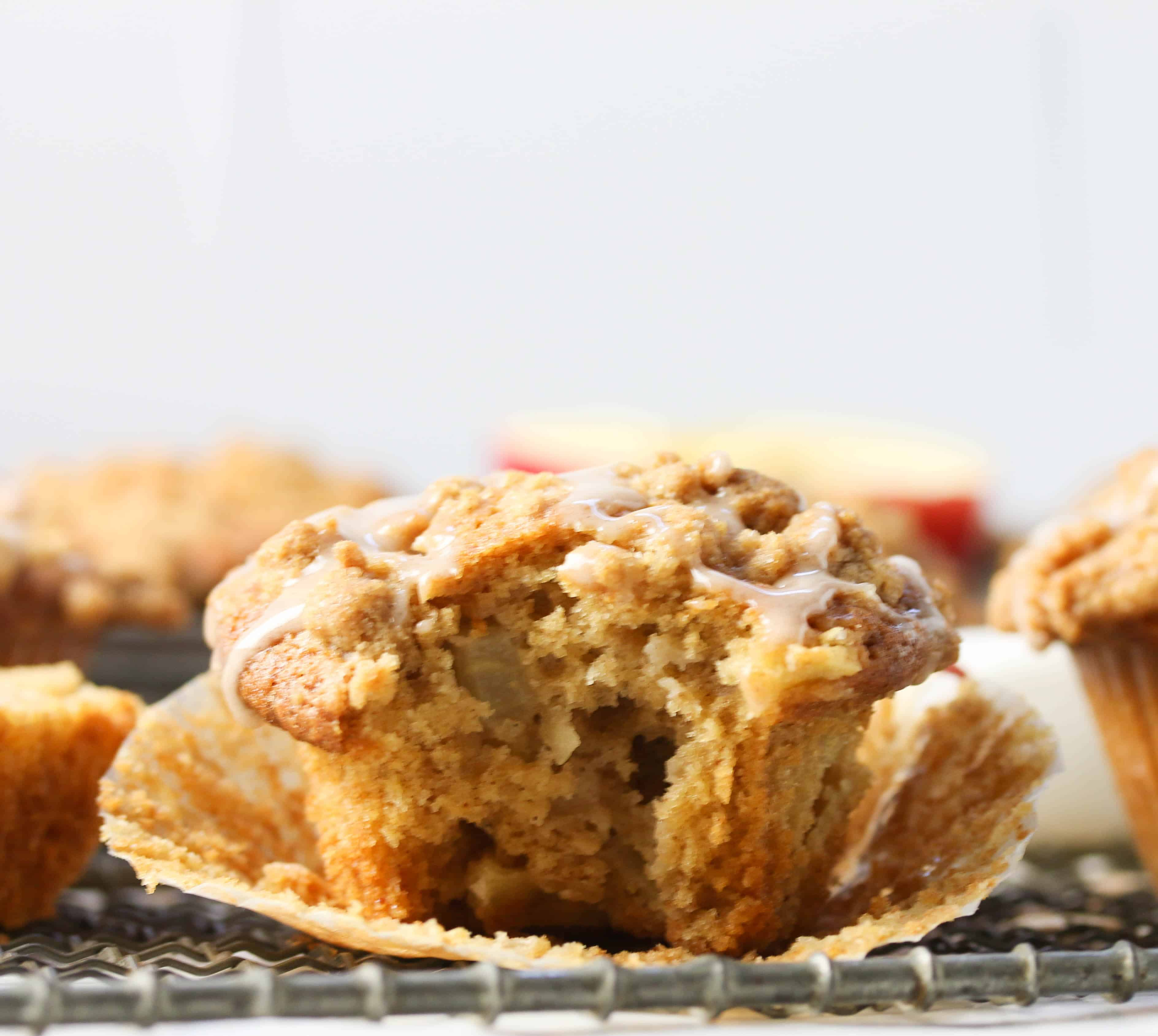 apple crumb muffin with liner peeled back and bite taken out of it