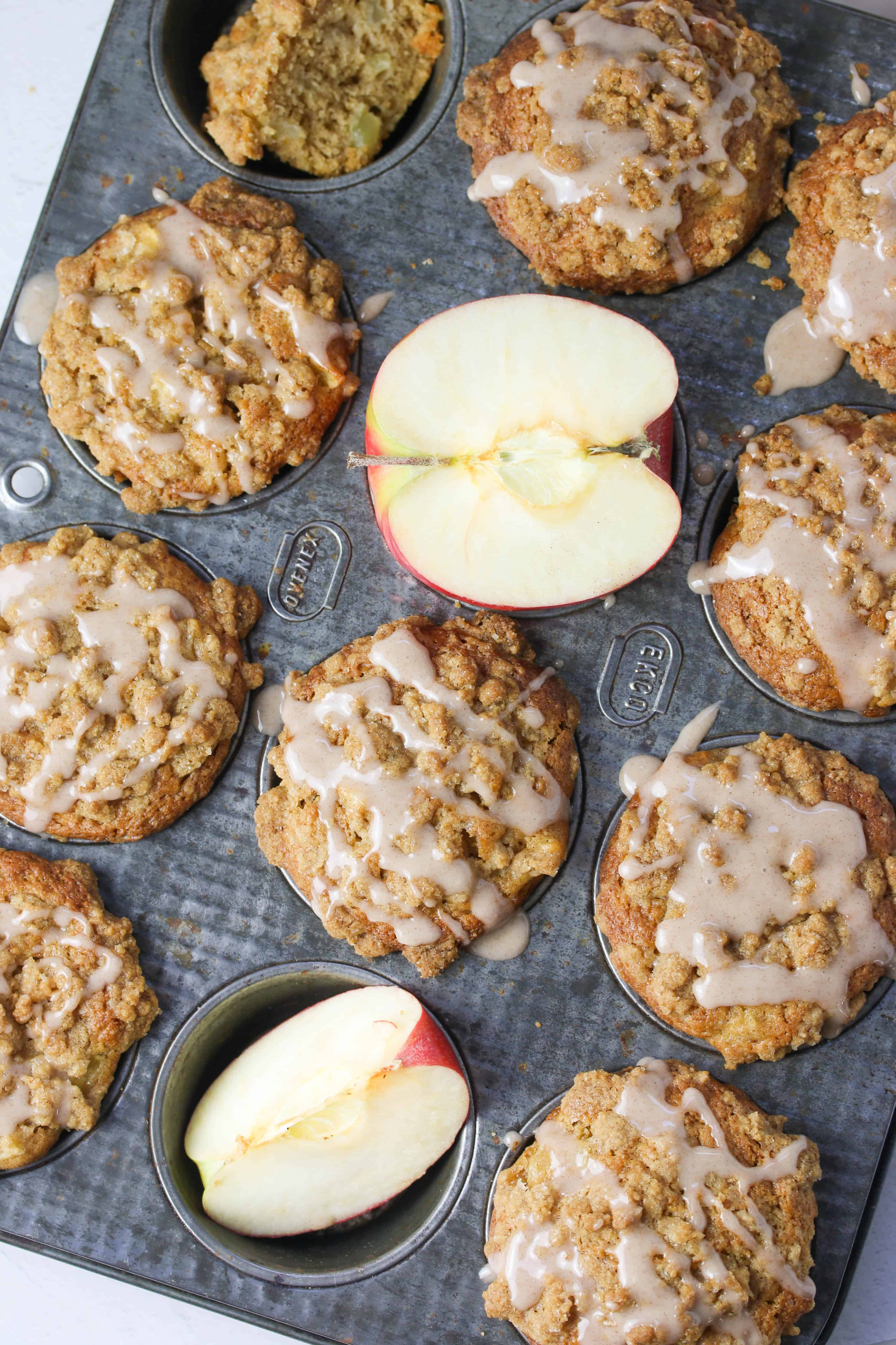 baked apple crumb muffins in tin with glaze drizzled on
