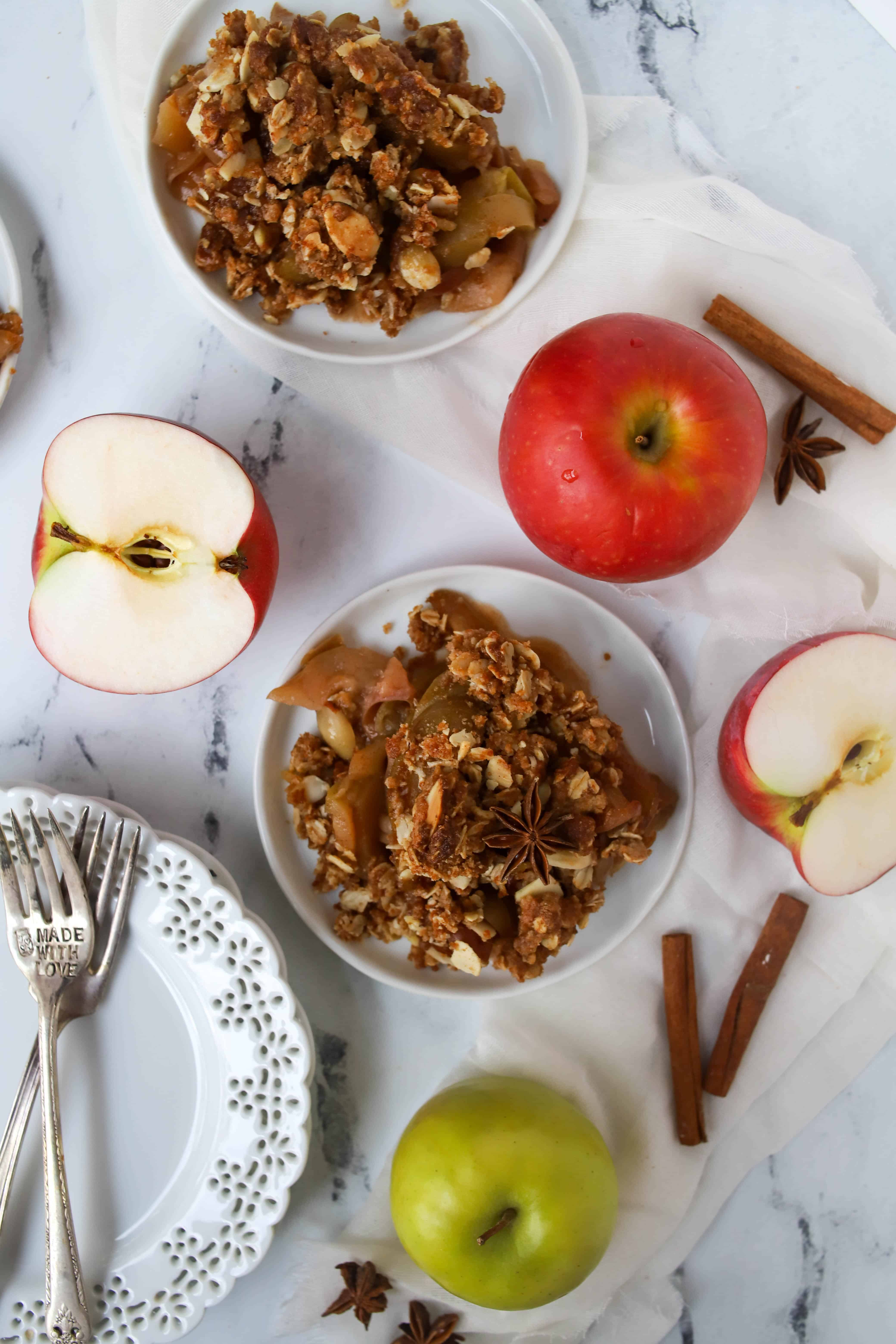 two plates of apple crisp surrounded by apples and cinnamon sticks