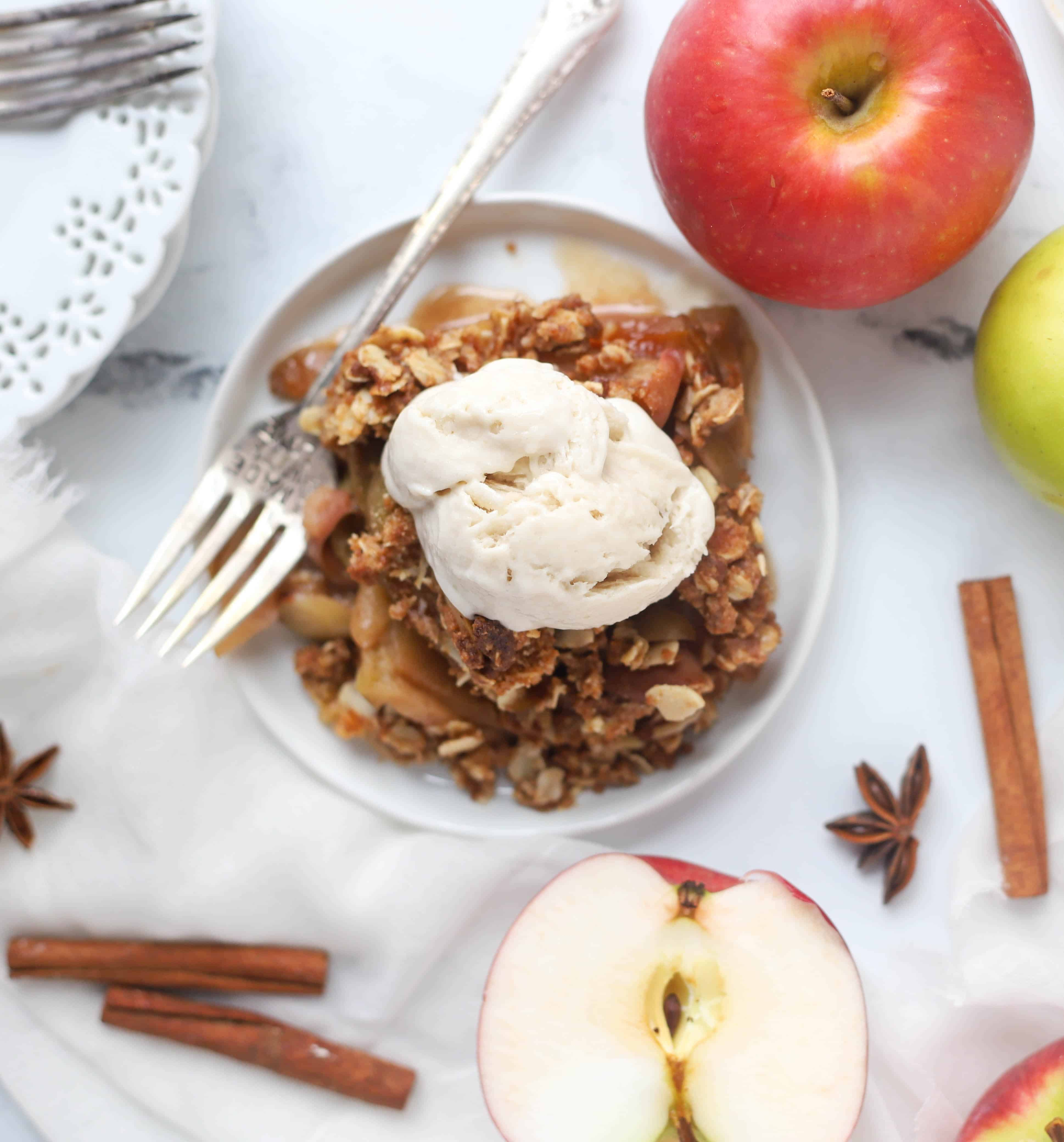 serving of apple crisp on a plate topped with ice-cream with a fork next to it