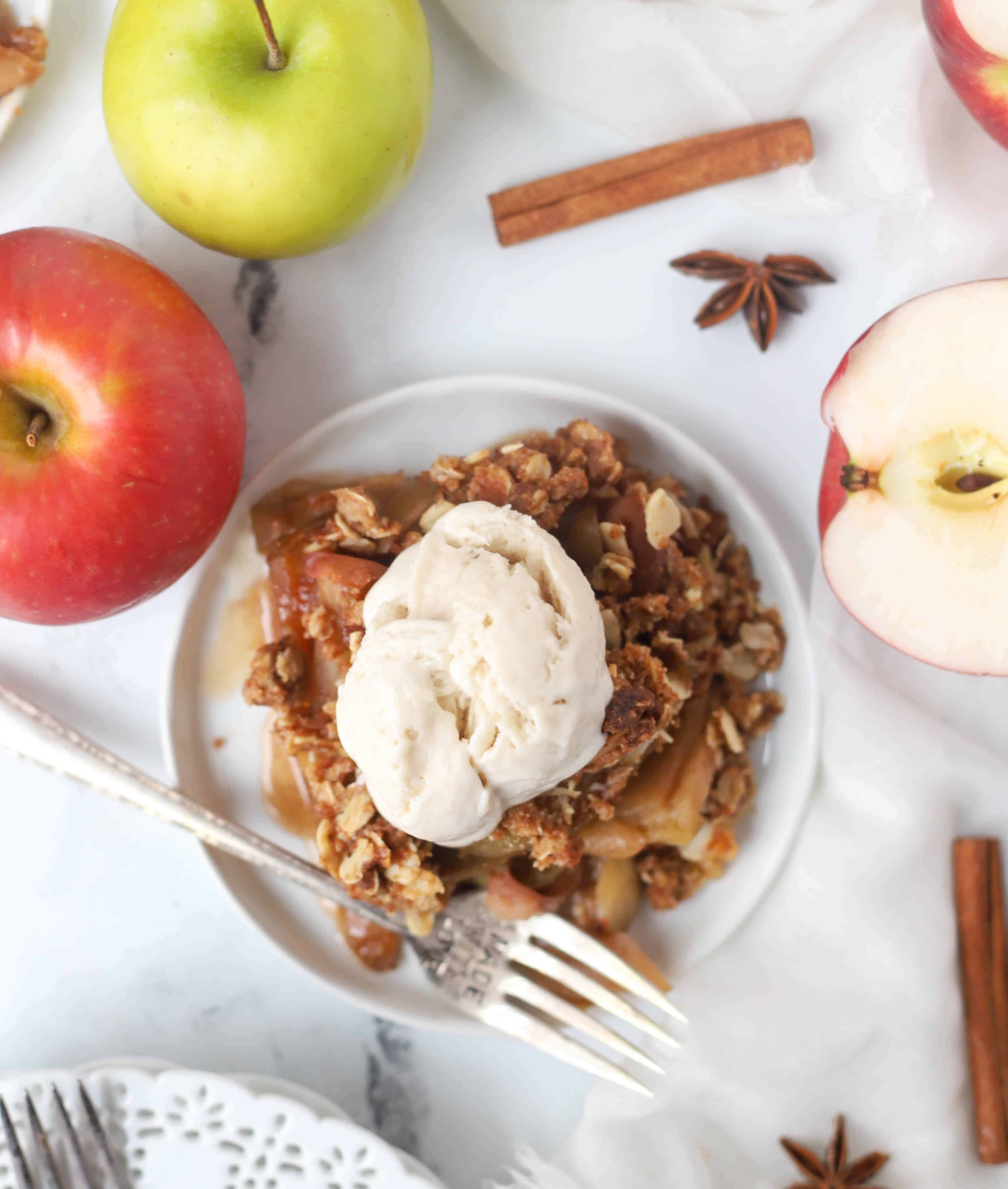 serving of apple crisp on a plate topped with ice-cream