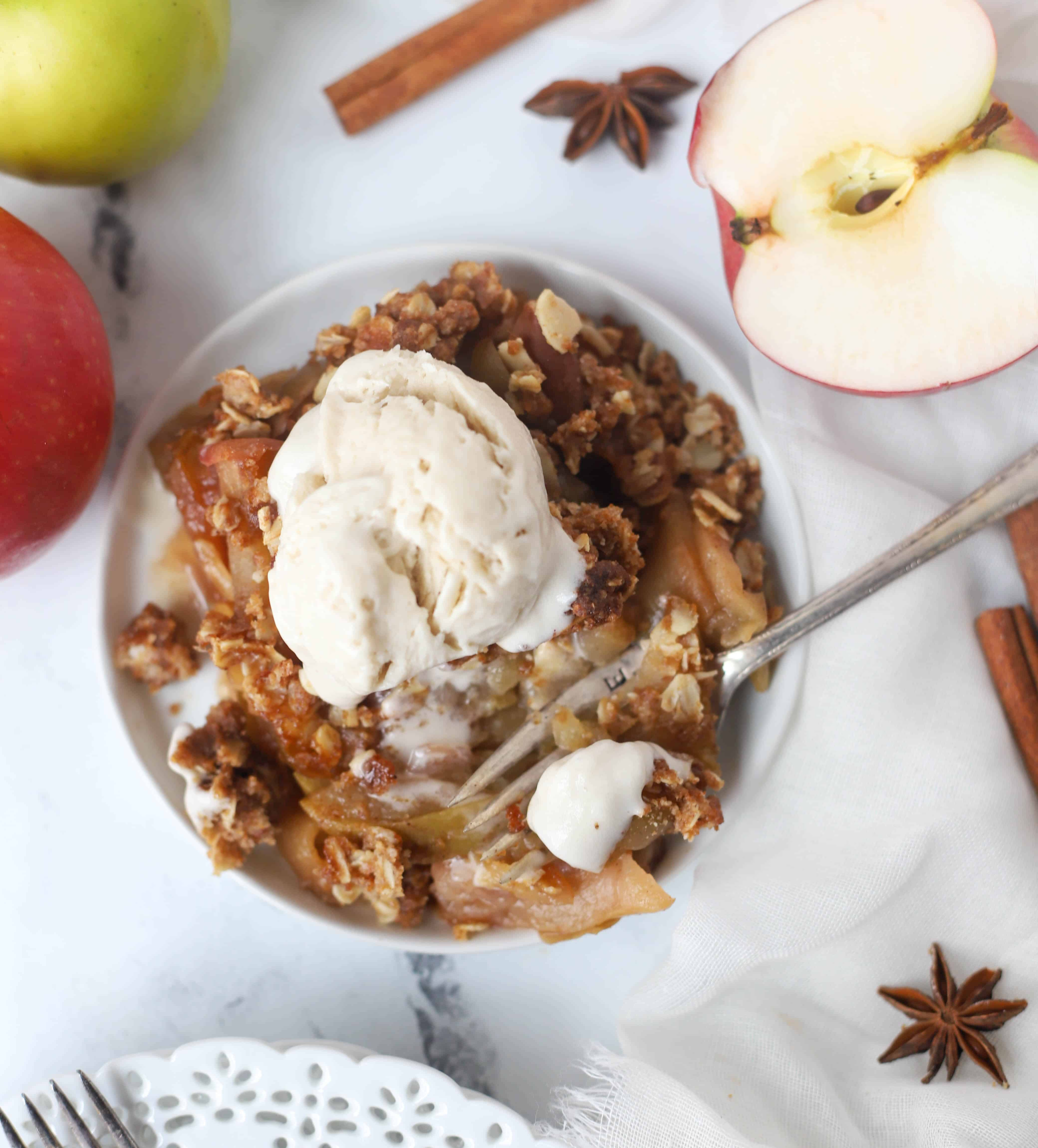 apple crisp on a plate topped with ice-cream
