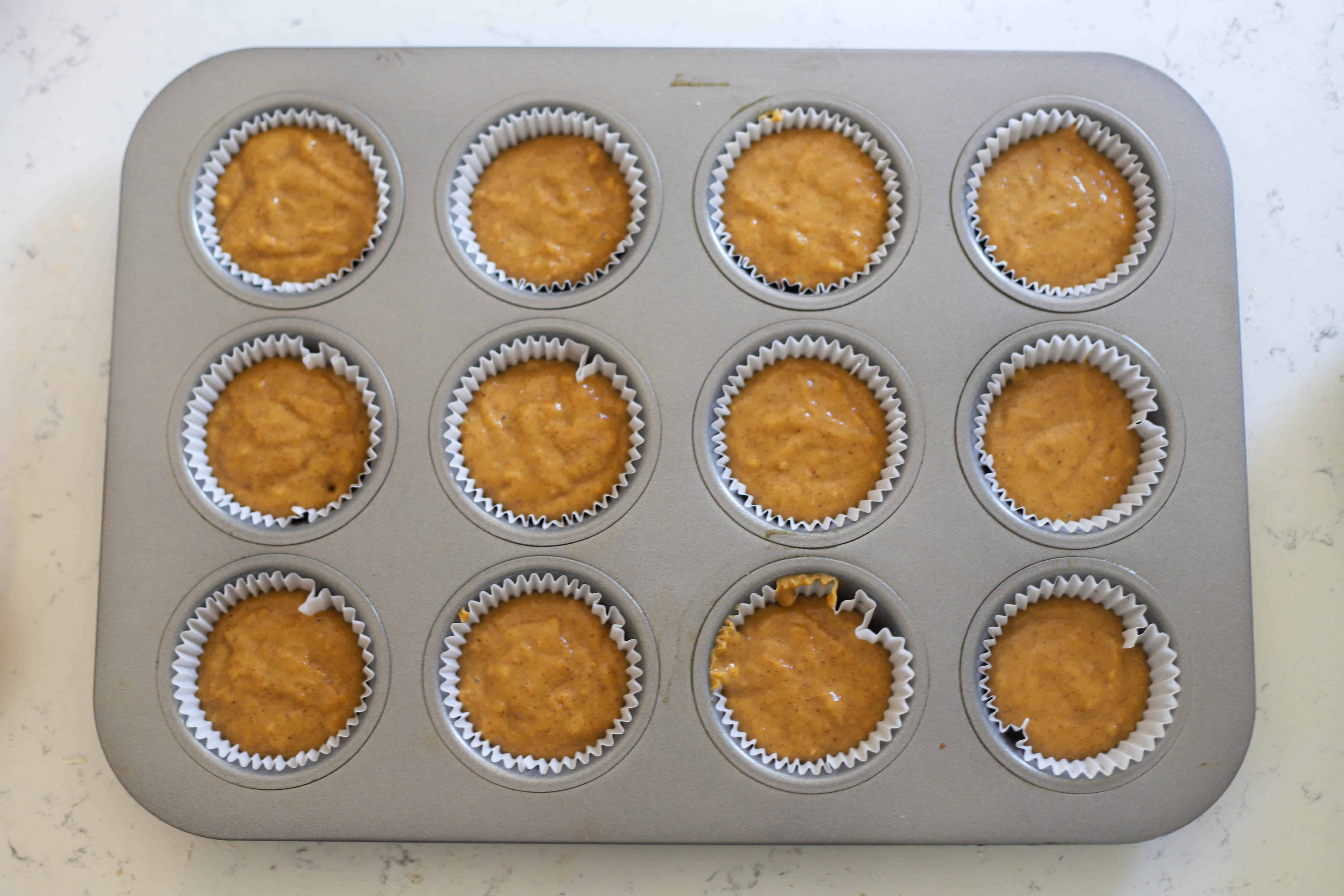 sweet potato muffin batter divided into muffin tin