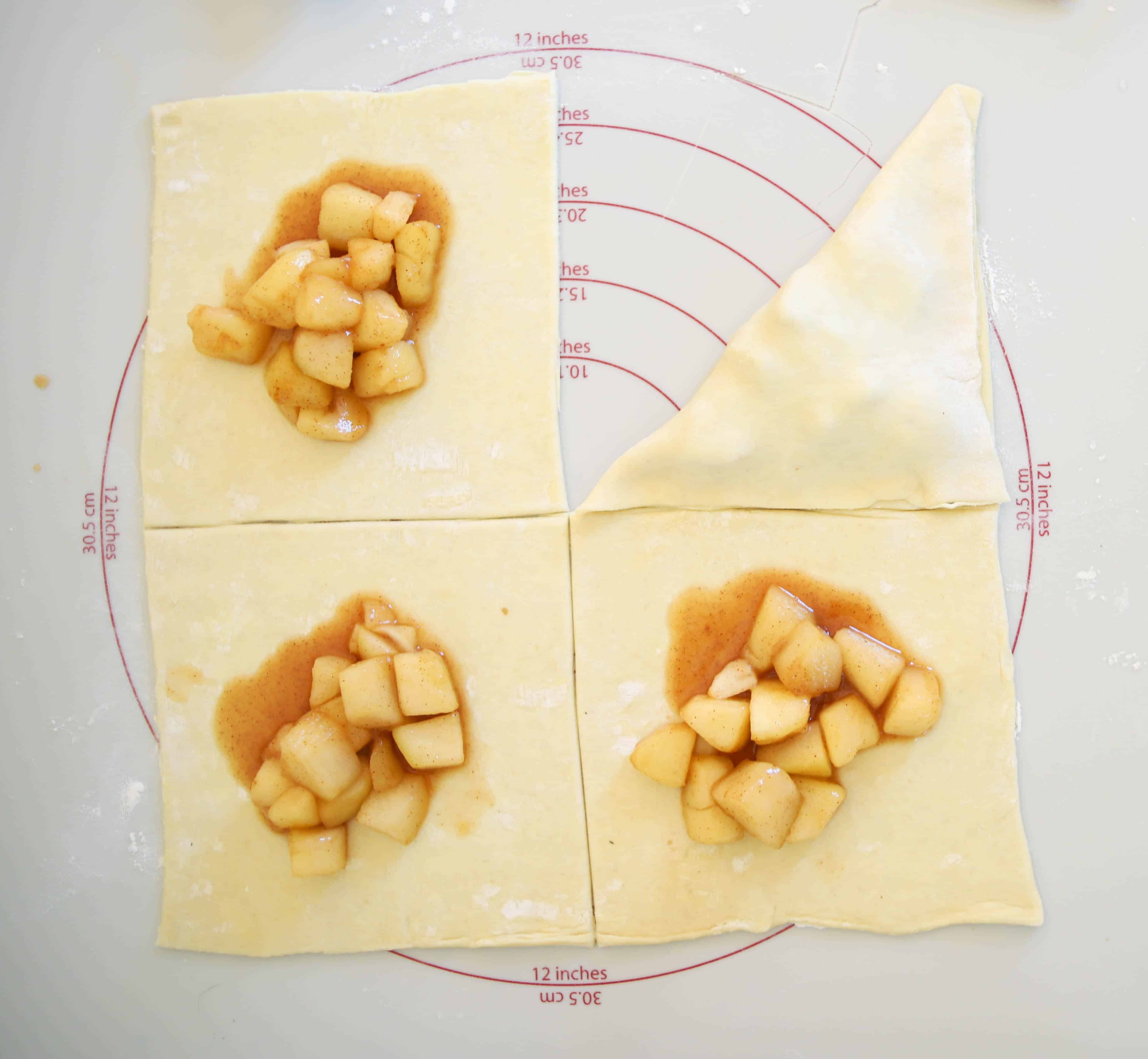 four squares of puff pastry with filling in the center, and one folded over to make a triangle